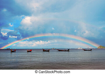 Blue sky background with rainbow on sea