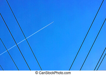 Blue sky, electrical wires and an airplane in the sky