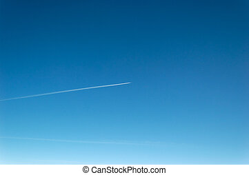 Blue Sky - Exhaust strip from a passing airplane against...