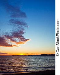 Blue sky - orange vibrant sunset over the calm empty beach