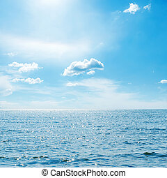 blue sky with clouds and sun over sea