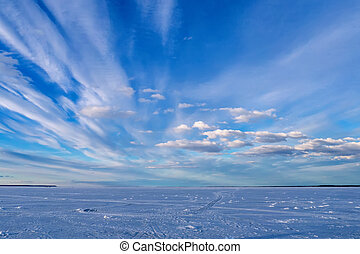 blue sky with clouds on a winter day over the ice of the river