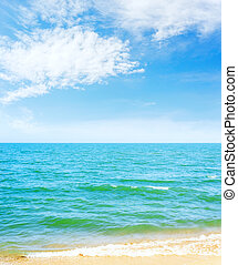 blue sky with clouds over sea and yellow sand