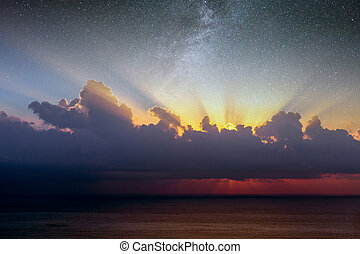 Blue sky with clouds, sea and sun on the horizon