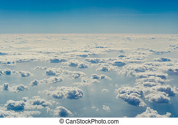 Blue sky with clouds, shot from an airplane. The upper layers of the atmosphere.