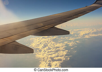 blue sky with clouds under the wing of an airplane