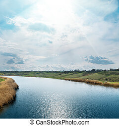 blue sky with sun and clouds over river with reflections