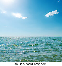 blue sky with sun and clouds over sea