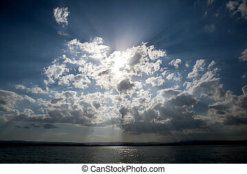 Blue sky with sun and dramatic clouds