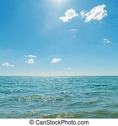 blue sky with sun over sea