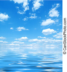 Blue sky with water reflection - Bright blue sky and puffy ...
