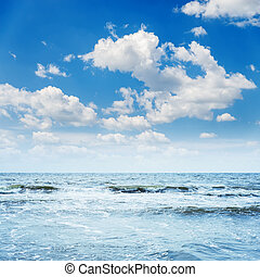 blue sky with waves and clouds over it