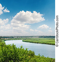 blue sky with white clouds over river in green riverside