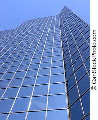Blue Skyscraper - A glass skyscraper reflects a clear blue...