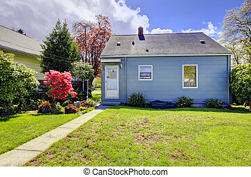 Blue small house with spring landscape from backyard with green grass. American house build in 1942.