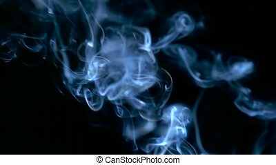 Blue smoke rising over black background in slow motion.