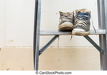 Blue sneakers on Aluminium ladder with wall dirty