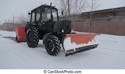 Blue snowplow removing snow sprinkled sand antifreeze