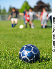 Blue Soccer Ball and Players - A blue soccer ball on field...