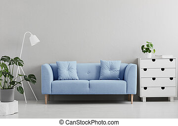 Blue sofa between white lamp and cabinet in grey living room interior with plants. Real photo