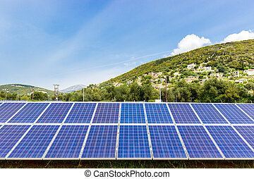 Blue solar collectors near town on mountain