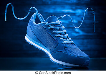 Blue sport sneakers on a wooden background