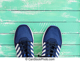 blue sport sneakers on green wooden background
