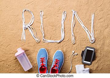 Blue sports shoes, bottle, smartphone against sand, studio...