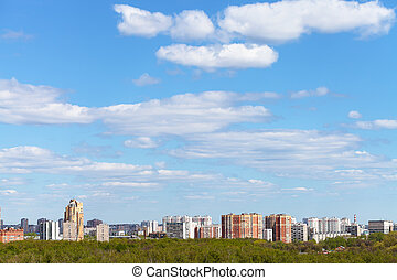 blue spring sky over city and green woods