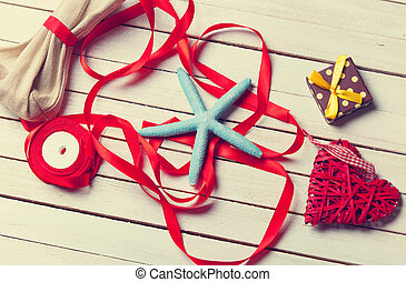 blue star, red ribbons and little gifts lying on the table