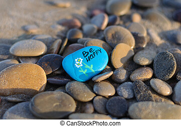 blue stone with the inscription be happy on the beach among the stones