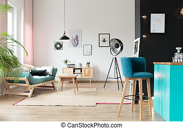 Blue bar stool in kitchen area in warm room with turquoise settee with pillows and table on carpet
