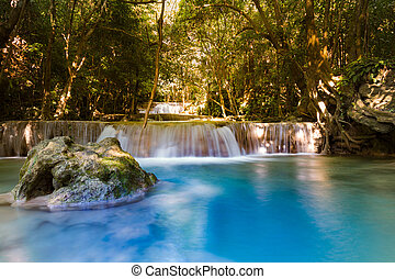 Blue stream waterfall in deep forest jungle