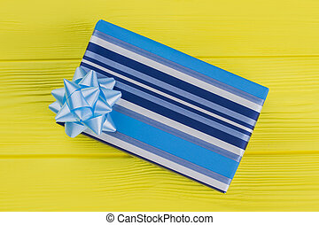 Blue striped gift box on yellow wood.