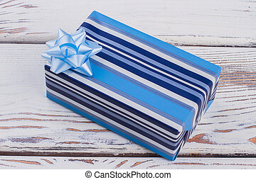 Blue striped gift box with bow.
