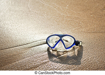 Blue swimming mask on sea beach