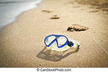 Blue swimming mask on sea beach