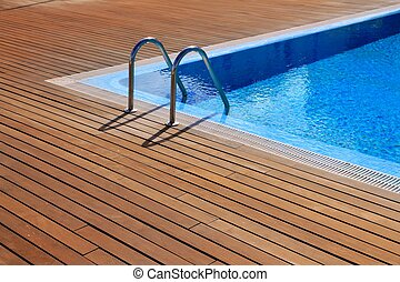 blue swimming pool with teak wood flooring stripes summer...