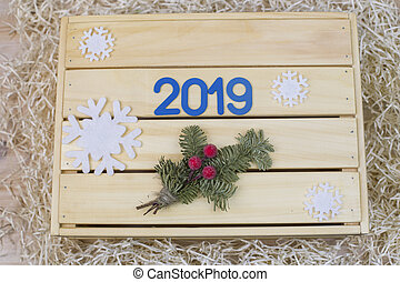 Blue symbol with and spruce twig on a wooden background with snowflakes