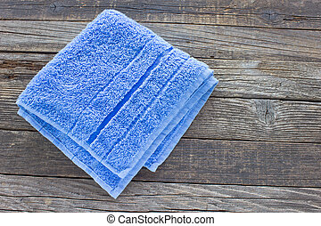 Blue towel on wooden background