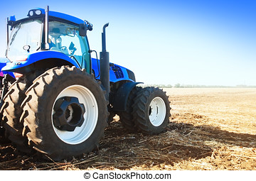 Blue tractor in a field on a bright sunny day