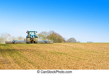 blue tractor ploughing the fields in spring