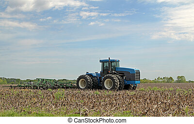 Blue Tractor Plowing - Blue tractor pulling plow in a farm...