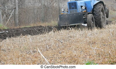 Blue tractor plows steel ground furrows in late autumn in...