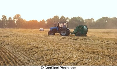 Blue tractor riding around on the field.