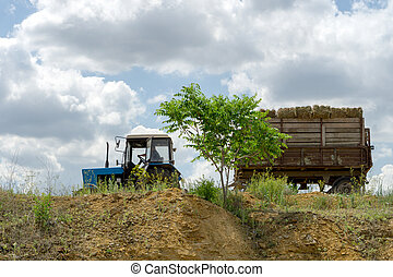 Blue tractor with hay in a trailer rides on the edge of a cliff