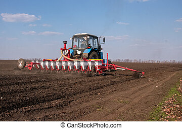 Blue tractor with red sower on the field in bright sunny...