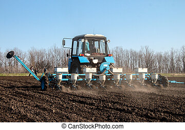 Blue tractor with sower on the field in bright sunny spring morning