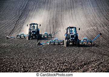 Blue tractors with sowers on the field in bright sunny spring morning