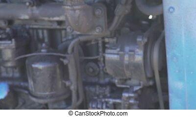 Blue traktor Belarus black engine motor in working summer...